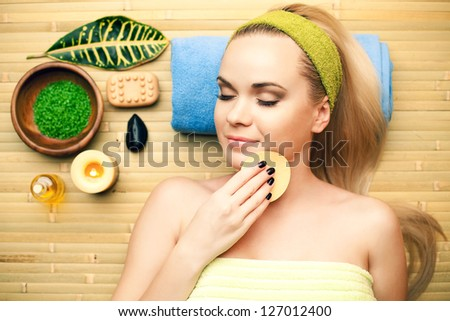 Portrait of a beautiful young woman touching her face with a special sponge at a spa salon. Perfect Skin. Skincare. Young Skin