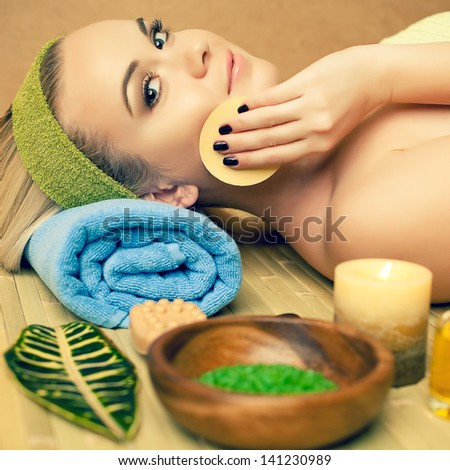 Portrait of a beautiful young woman touching her face with a special sponge at a spa salon. Perfect young skin and hair. Skincare and haircare. Close up. Indoor shot