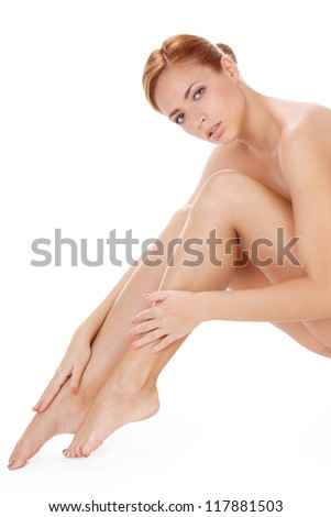 portrait of a beautiful young woman touching her legs isolated over white background