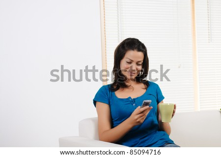 Portrait  of a beautiful young woman using a mobile phone with a  cup of coffee.