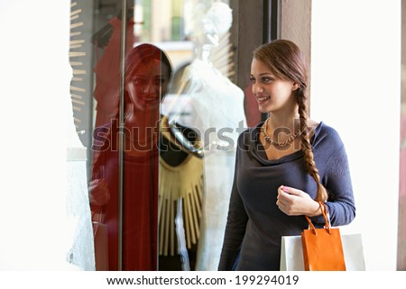 Portrait of a beautiful young woman visiting a luxury store display window with manikins and exclusive fashion during a sunny holiday, smiling. Shopping and consumer lifestyle, outdoors.