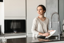 Portrait of a beautiful young woman washing dishes at the kitchen at home