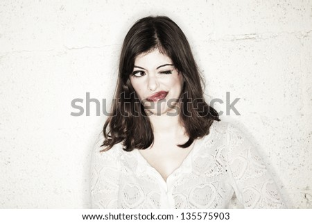 Portrait of a beautiful young woman wearing an exaggerated winking face, looking to the side with her eye that was left open.
