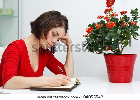 Portrait of a beautiful young woman wearing red top, sitting at home at her desk, looking down and writing, green and red flowers in red pot