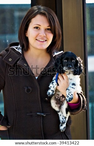 Portrait of a beautiful young woman with a Cocker Spaniel puppy.