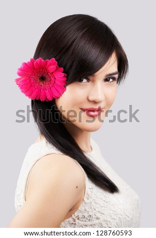 Portrait of a beautiful young woman with a flower in her hair isolated on grey