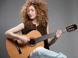 Portrait of a beautiful young woman with a guitar. She sings a song. Close-up.