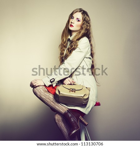 Portrait of a beautiful young woman with a handbag. Fashion photo