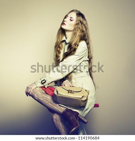 Portrait of a beautiful young woman with a handbag. Fashion photo
