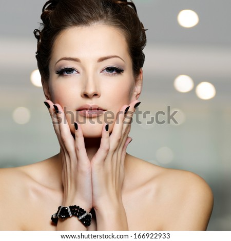 Portrait of a beautiful young woman with black nails