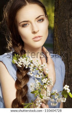 Portrait of a beautiful young woman with braid hairdo and flower in her hand, outdoors