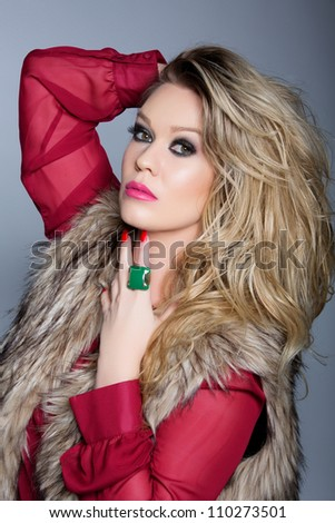 portrait of a beautiful young woman with curly blond hair and glamour make-up with pink lips wearing a fashion red blouse and a faux fur coat