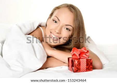 Portrait of a beautiful young woman with gift in white bed