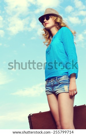 Portrait of a beautiful young woman with her old suitcase against the blue sky. Fashion shot.