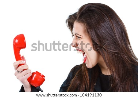 Portrait of a beautiful young woman with long brown hair, screaming into a red retro telephone receiver - isolated on white