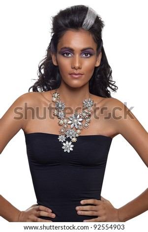 portrait of a beautiful young woman with long curly hair and tanned skin wearing an expensive necklace and black dress.