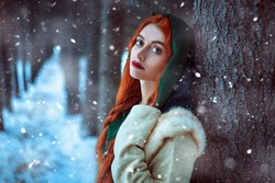 Portrait of a beautiful young woman with long red hair wearing medieval clothes walks through a winter snowy forest. Historical reconstruction of the early Middle Ages. Christmas tale.