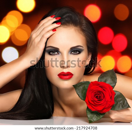 Portrait of a beautiful young woman with red lips,  nails and rose flower in hand. Fashion model with black eye makeup posing at studio over night lights balls.