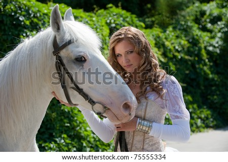 Portrait of a beauty elegant young woman with wavy long hairs in refined white clothing and beautiful horse on a green ivy background