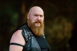 Portrait of a biker man and bear, strong and with a big beard. Looking at the camera with serious and hard expression. In a field background. concept of bikers and tough guys