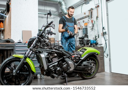 Portrait of a biker or repairman in working overalls standing near the motorcycle during the repairment in the workshop