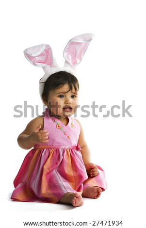 Portrait of a biracial baby girl with a pair of large bunny ears on her head.  Isolated on white.