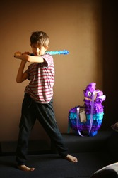 Portrait  of a birthday boy with a bat planning to break lama pinata