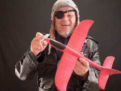 portrait of a bizarre elderly man has in his hands red airplane and propeller spinner torque. fancy pensioner with gray beard and black blindfold in one eye. weird people.