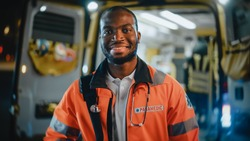 Portrait of a Black African American EMS Paramedic Proudly Standing in Front of Camera in High Visibility Medical Orange Uniform and Smiling. Successful Emergency Medical Technician or Doctor at Work.