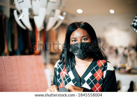 portrait of a black female shopkeeper at work wearing a protective face mask against viruses. New normal concept. Photo stock ©