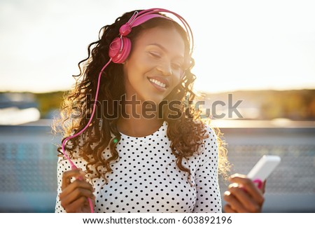 Portrait of a black lady enjoying the music on her phone
