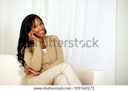 Portrait of a black woman smiling at you while sitting on sofa and speaking on mobile phone at home indoor