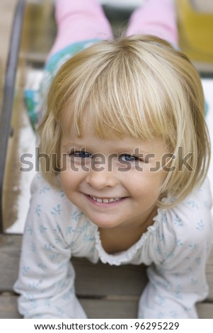 stock photo : Portrait of a blond beautiful little 4 year old girl coming down the slide. Positive feeling.