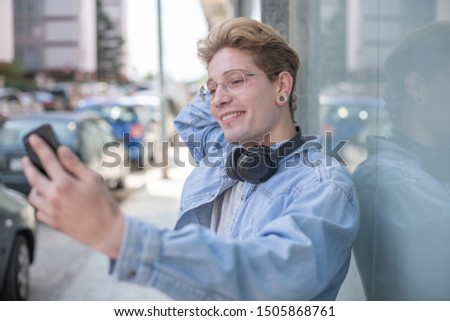 Portrait of a blond boy with glasses and headphones taking a picture of himself with his smartphone in the street. Concept of technological youth. Close-up