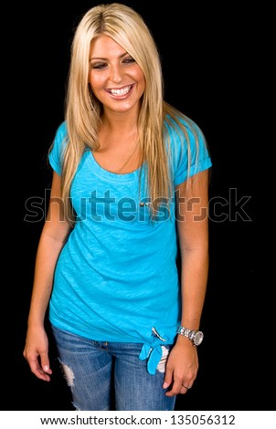 Portrait of a blonde Caucasian female with brown eyes in a blue shirt, ripped blue jeans on black background.