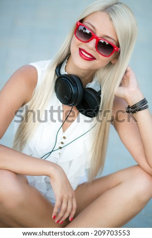 Portrait of a blonde girl with black sunglasses and headphones. closeup portrait of a sexy beautiful woman posing in headphones outdoors