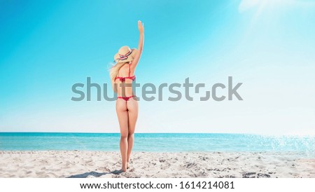 Portrait of a blonde in pink glasses at the sea. A woman walks along the beach and enjoys.