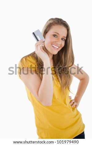 Portrait of a blonde student showing a credit card against white background