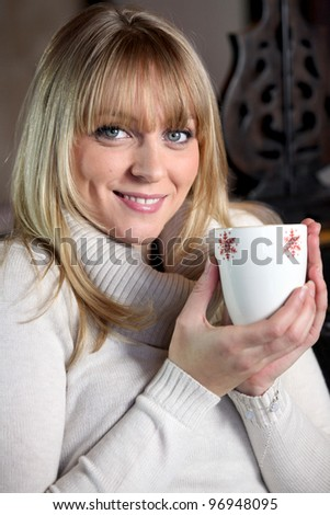 Portrait of a blonde woman drinking a hot drink