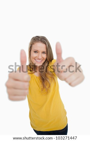 Portrait of a blonde woman the the thumbs-up against white background - stock photo