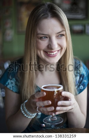Portrait of a blonde woman with blue eyes drinking a goblet of beer.