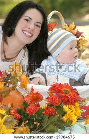 Portrait of a blue eyed baby boy in a basket outdoors, surrounded by fall leaves and flowers, in a park setting