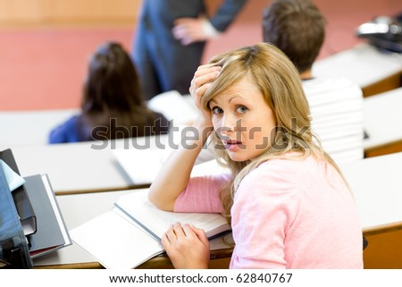 Portrait of a bored female student during a university lesson in an auditorium
