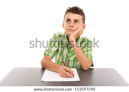 Portrait of a bored schoolboy doing his homework at the desk, isolated on white background