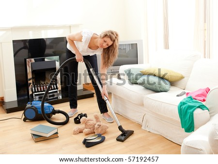 Portrait of a bored woman vacuuming at home