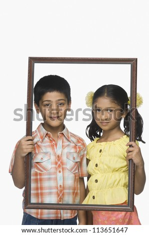 Portrait of a boy and a girl holding an empty picture frame