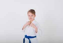 portrait of a boy blond in a white kimono with a blue belt with hands in protection on a white background with a place for text