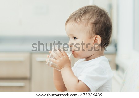 Portrait of a boy drinking a glass of water,happy in the kitchen