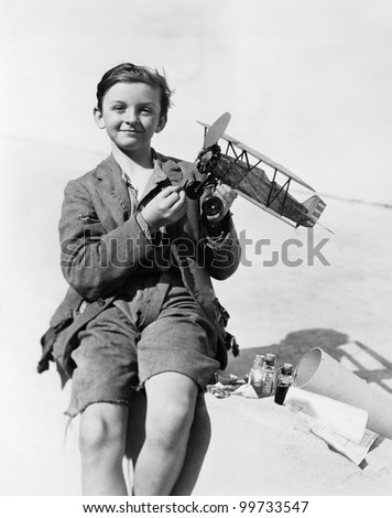 Portrait of a boy holding a model airplane and smiling