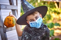 Portrait of a boy in a carnival costume for Halloween. Children wearing masks to protect against COVID-19.